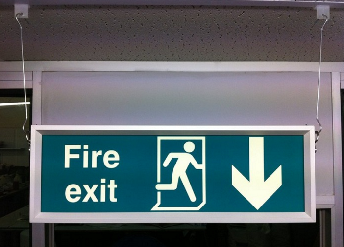 green reflective hanging fire exit sign light